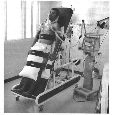 Figura 01: Paciente submetido ao ortostatismo passivo por meio da prancha ortostática.Fonte: (SARMENTO, 2009)